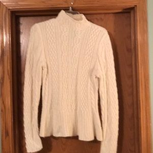 Cream colored cable knit sweater.
